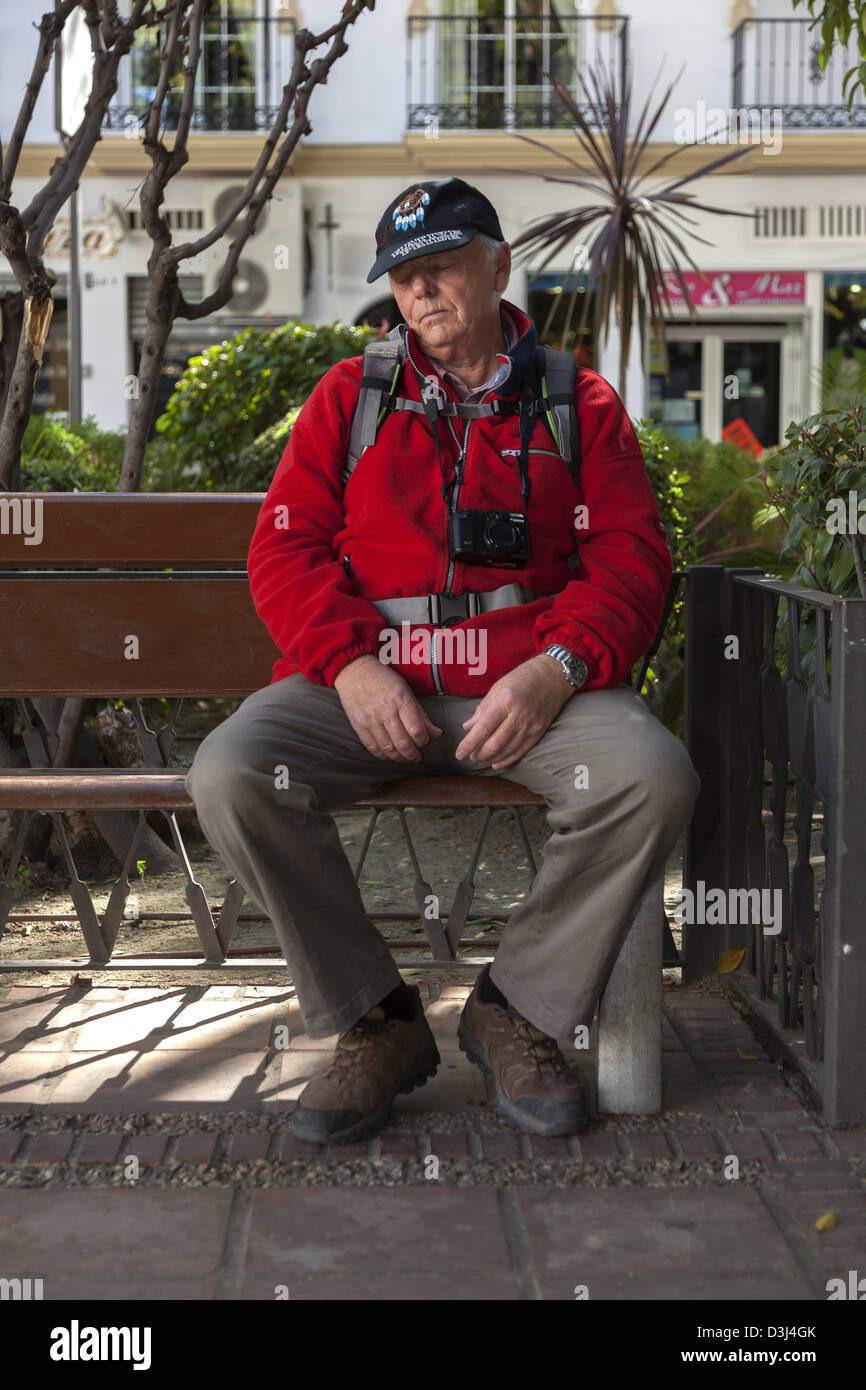 Senior male with a camera round his neck and a back pack snoozes on a park bench - Stock Image
