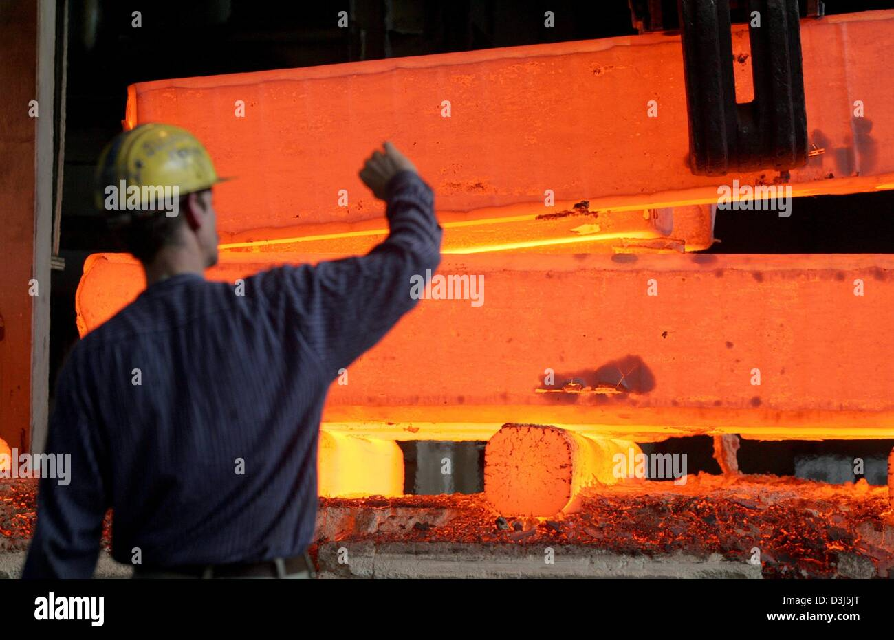 (dpa) - A worker holds his hand up protecting himself from the heat of a glowing block steel at the Edelstahlschmiede Stock Photo