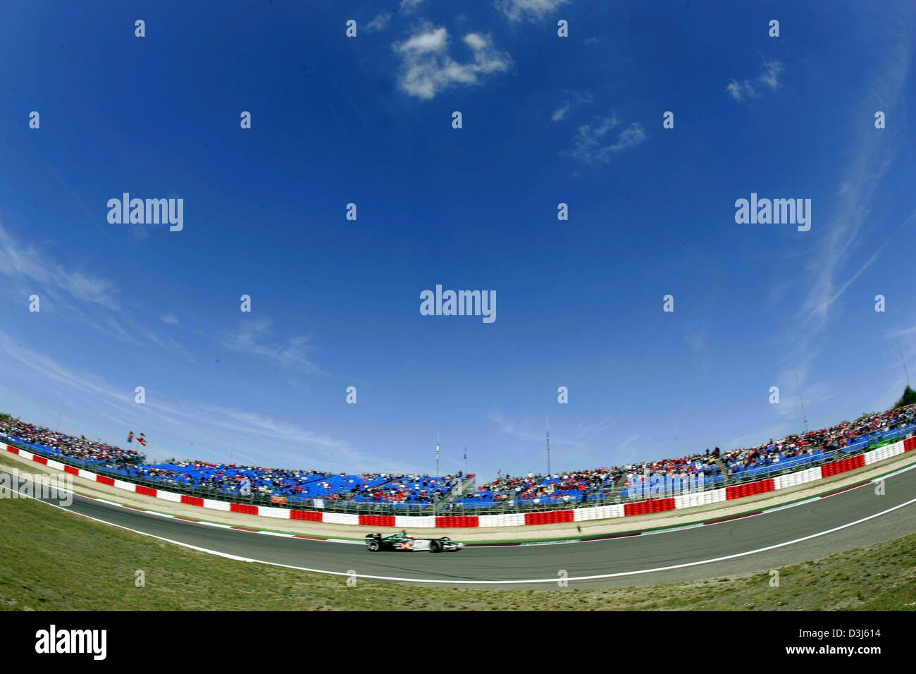(dpa) - A Formula 1 race car drives through a curve under a blue sky at the Nuerburgring race course in Germany, - Stock Image