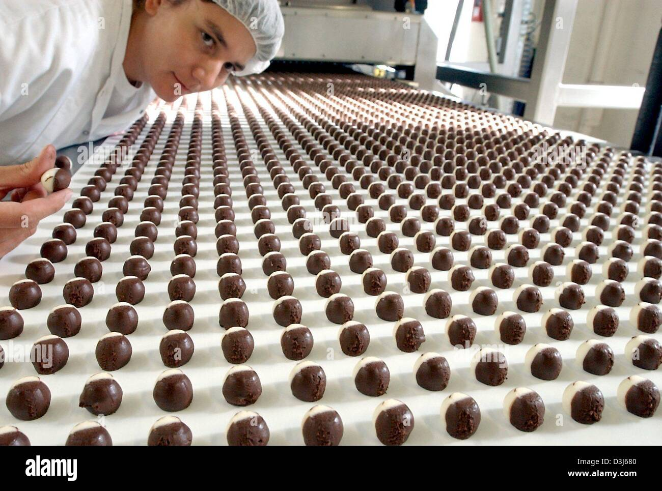 (dpa) - An employee supervises the production process at Germany's oldest chocolate factory, the Halloren chocolate - Stock Image