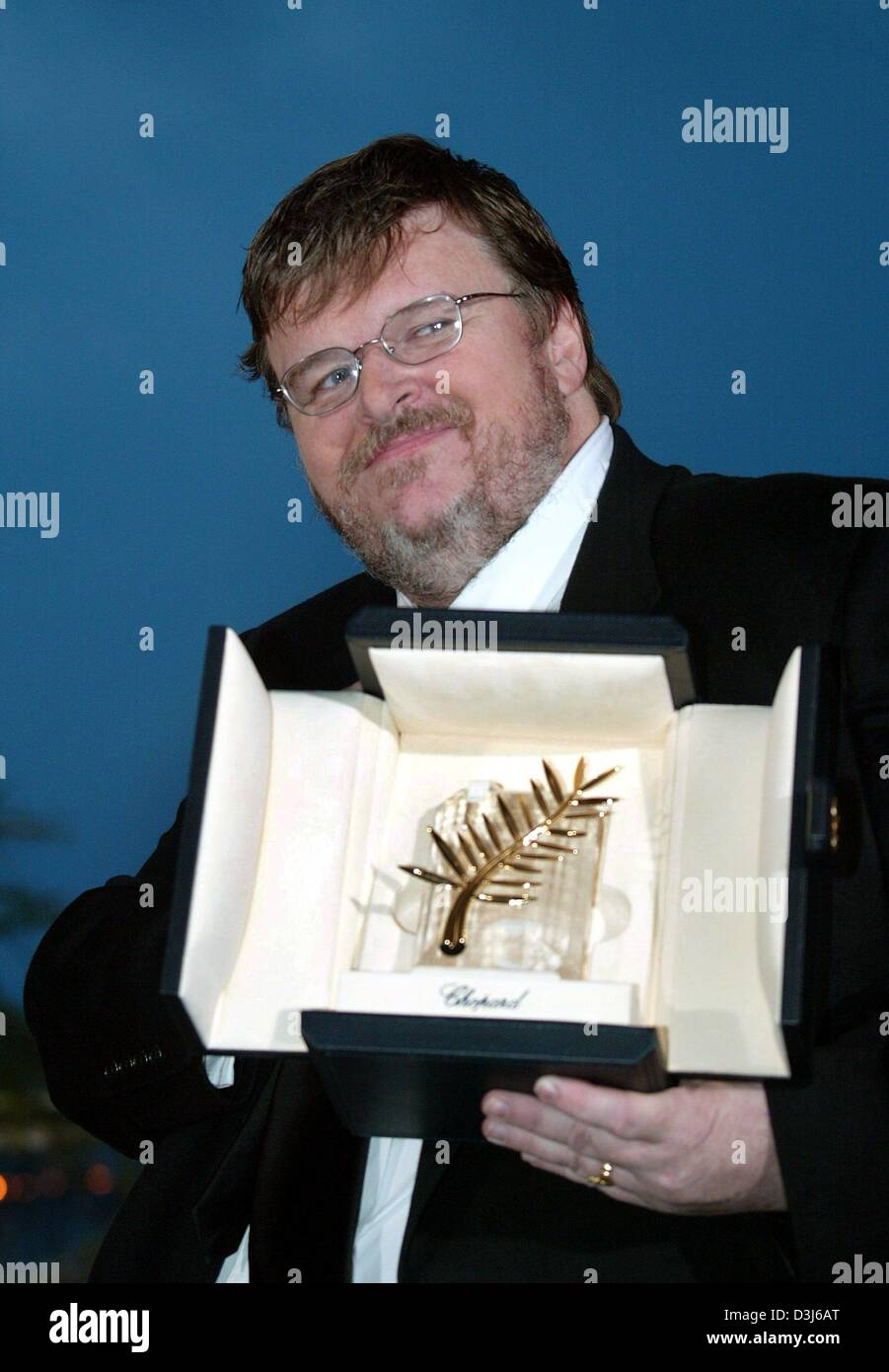 (dpa) - US film director Michael Moore shows his Golden Palm Award during a photocall after the awards show at the Stock Photo