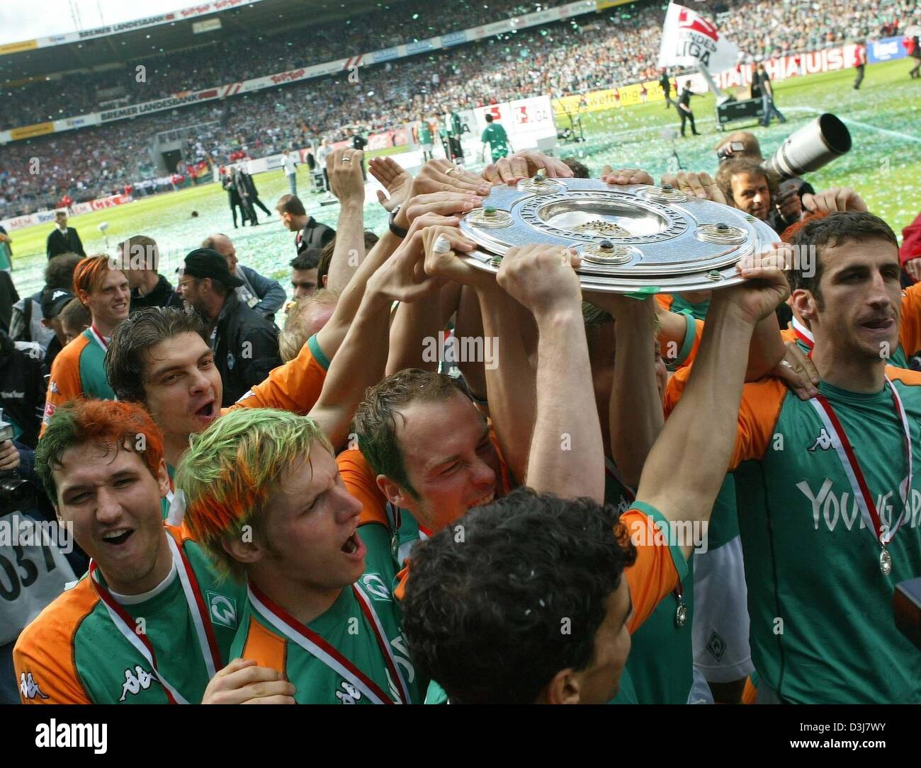 (dpa) - Bremen's soccer players cheer and jubilate as they carry the German Bundesliga trophy across the pitch after Stock Photo