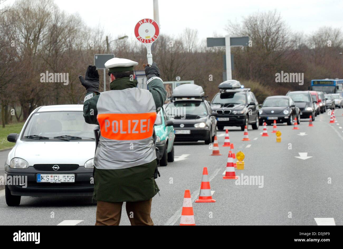 (dpa) - A police officer gestures as he instructs a car to pull over during a routine control on a road in Kassel, Stock Photo