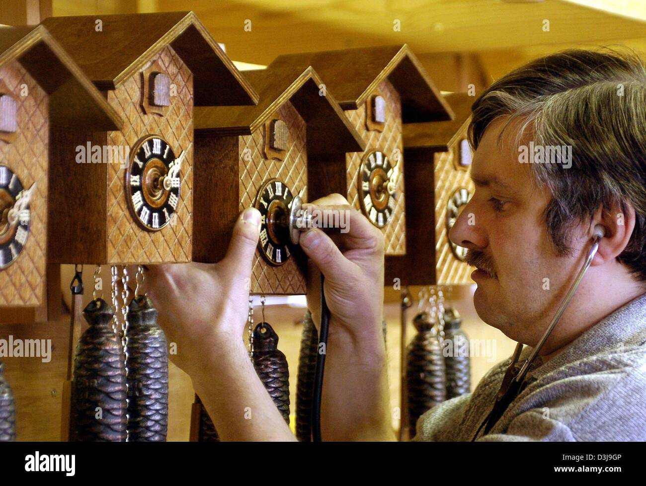 (dpa) - Precision mechanic Uwe Bergmann with a stethoscope examines the time of a cuckoo clock at a clockmaker in - Stock Image