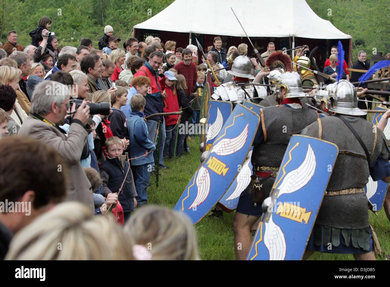 Members of the English 'Roman Military Research Society' practice with their weapons and menace the spectators - Stock Image