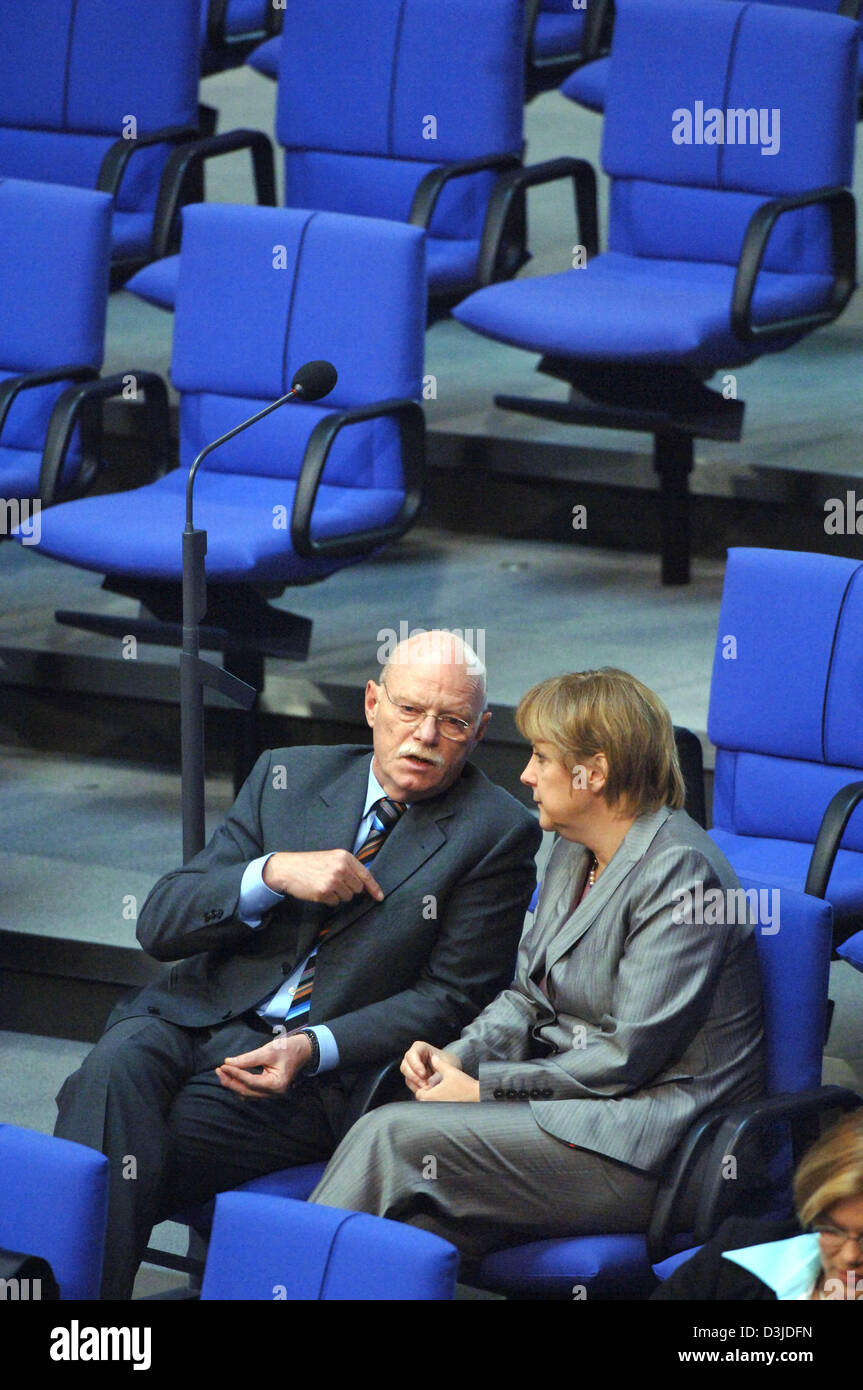 (dpa) - German Minister of Defence Peter Struck (L) and Chairwoman of the CDU, Angela Merkel, talk to each other at the German Bundestag parliament in Berlin, Thursday, 12 May 2005. The lower house debated the European Union constitution in today's parliamentary session. The constitution would allow the EU to be more decisive and at the same time remain governable. Stock Photo