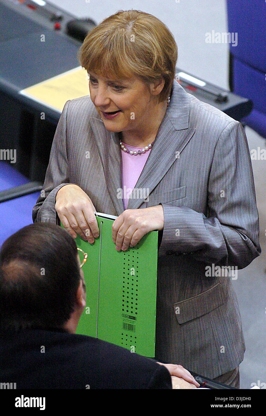 (dpa) - Angela Merkel, Chairwoman of the CDU, talks to a member of her fraction at the German Bundestag parliament in Berlin, 12 May 2005. The lower house debated the European Union constitution in today's parliamentary session. Stock Photo