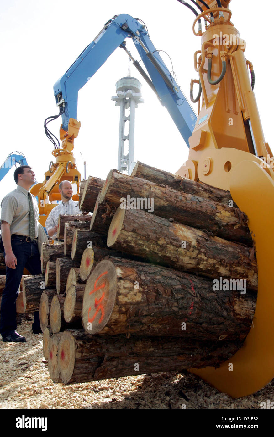 Two men watch an orange machine carrying a bulk of logs at the premiere of the world forest and wood product fair - Stock Image