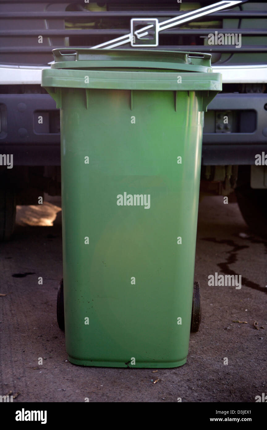 Green Wheelie bin standing in front of the grill of a truck that is used for the collection of recyclable materials - Stock Image