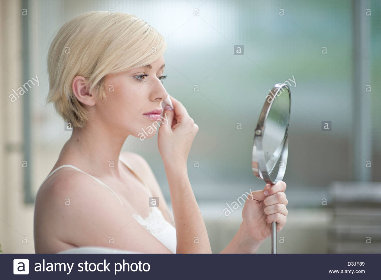 Young beautiful woman with a cotton swab looking in the mirror - Stock Image