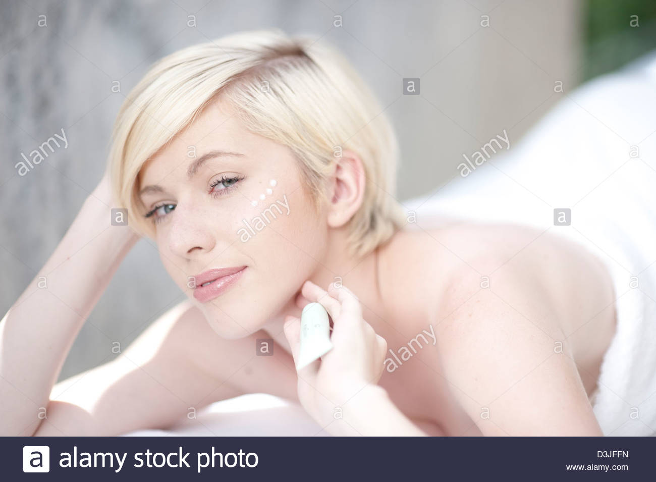 Young woman with anti wrinkle serum - Stock Image