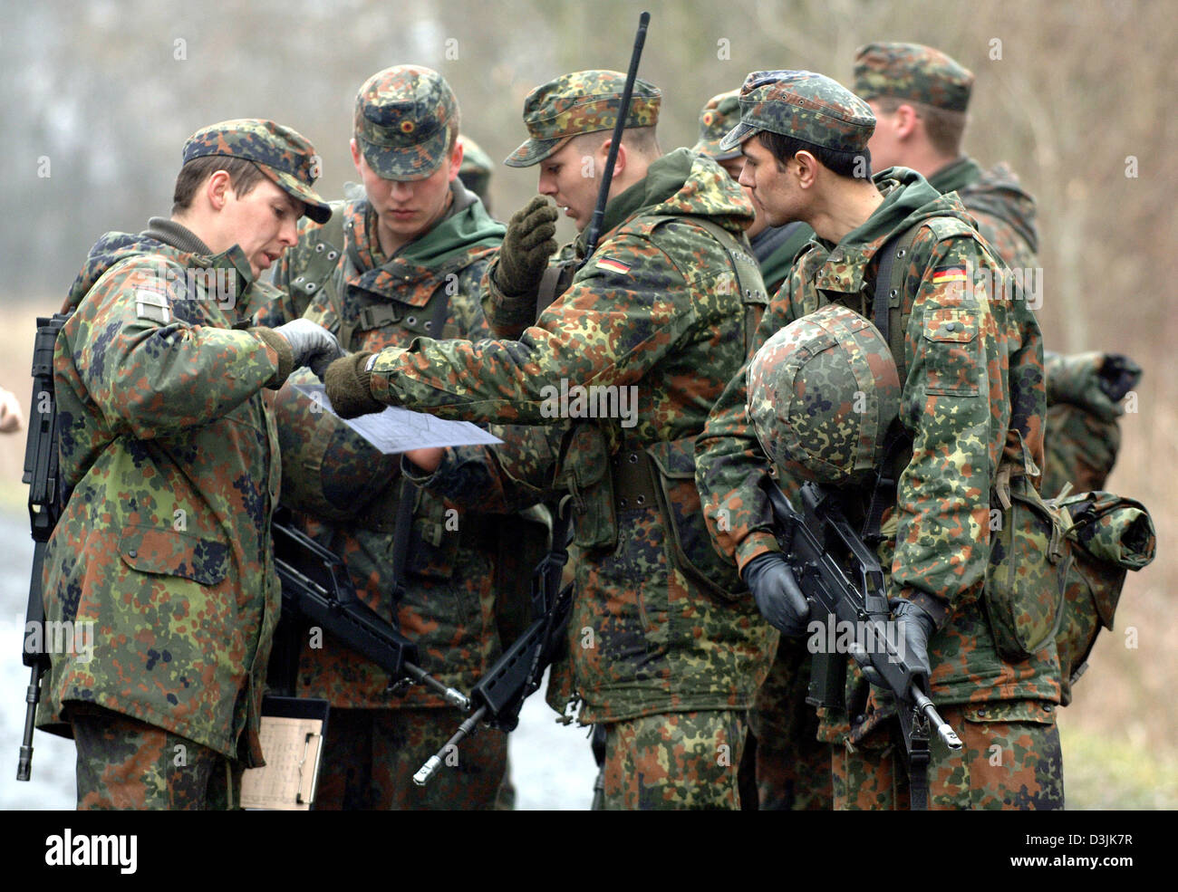 (dpa) - Recruits of the German Bundeswehr read a map at a training area in Ahlen, Germany, 18 March 2005. Within Stock Photo
