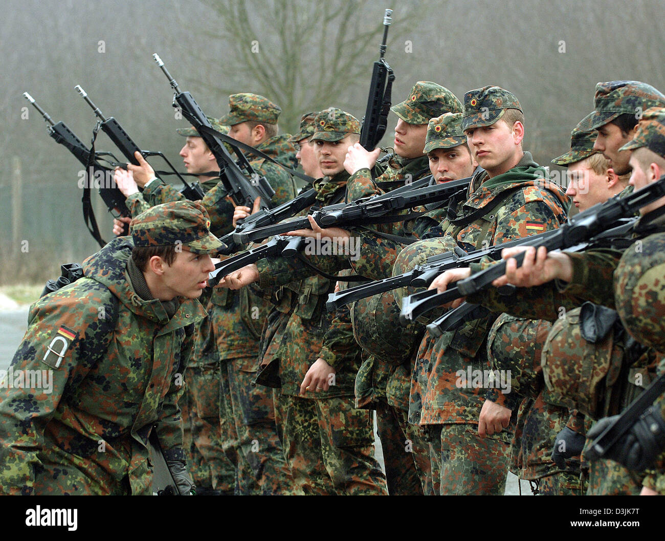 (dpa) - An instructor of the German Bundeswehr checks the recruits' emptied weapons (G 36) at a training area - Stock Image