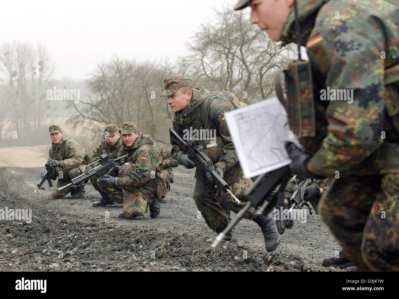 (dpa) - Recruits of the German Bundeswehr with guns of the G 36 type duck at a training area in Ahlen, Germany, - Stock Image