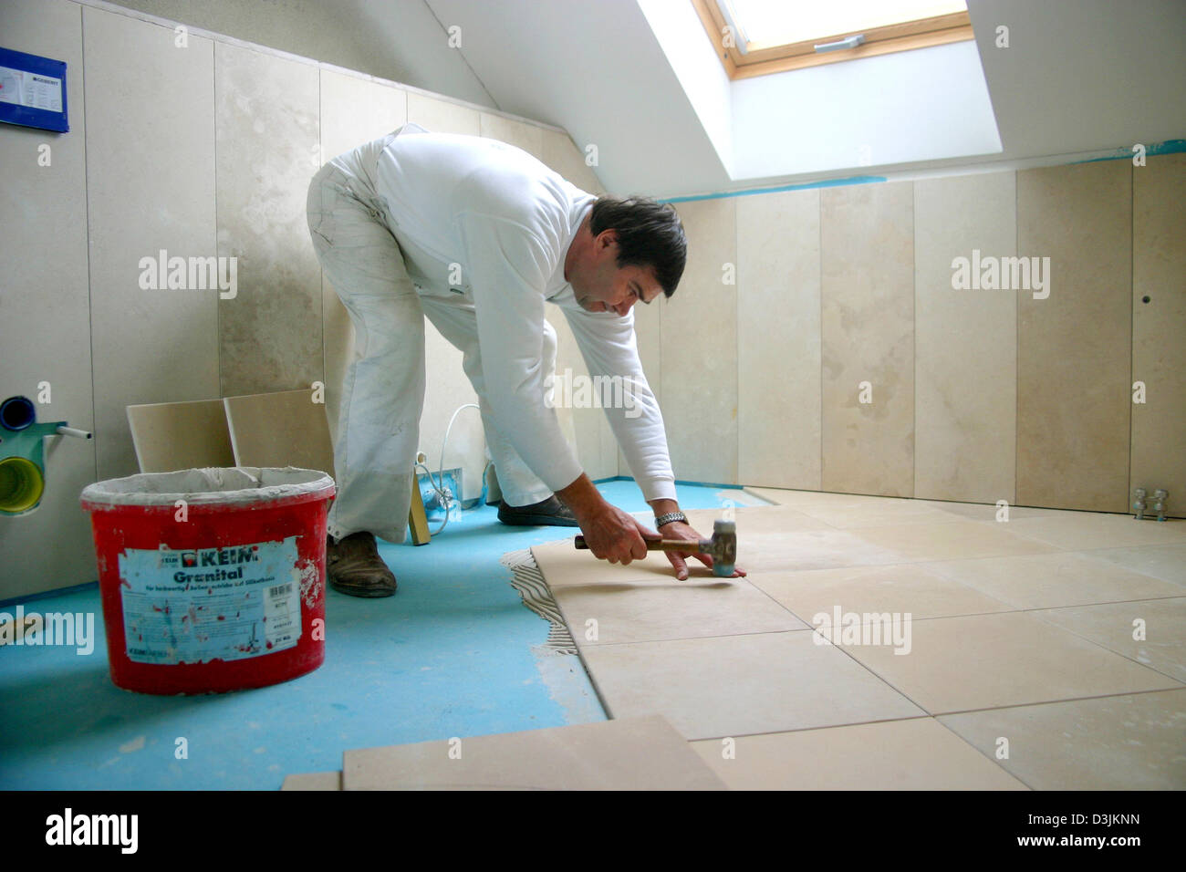 dpa) - A tiler tiles a bathroom at a construction site in Germany ...