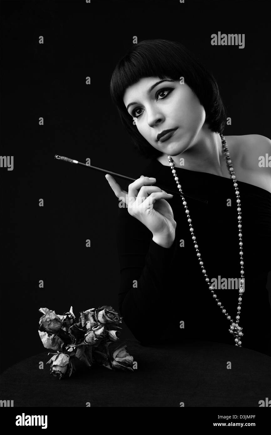 black and white: vintage styled portrait of a young beautiful woman with cigarette holder Stock Photo