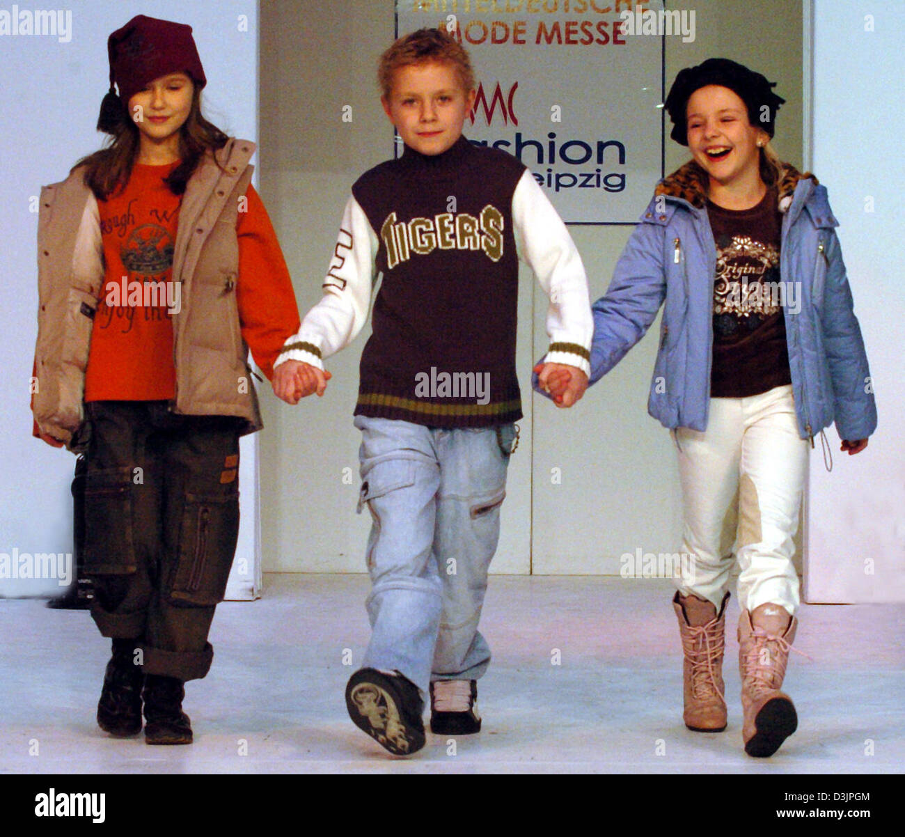 (dpa) - Children models (from L) Marie, Martin and Maria Antonia hold hands and smile as they walk down the catwalk Stock Photo