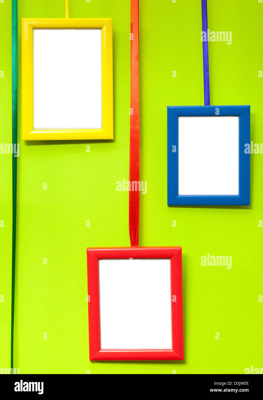 Colorful empty wooden frames on green wall - Stock Image