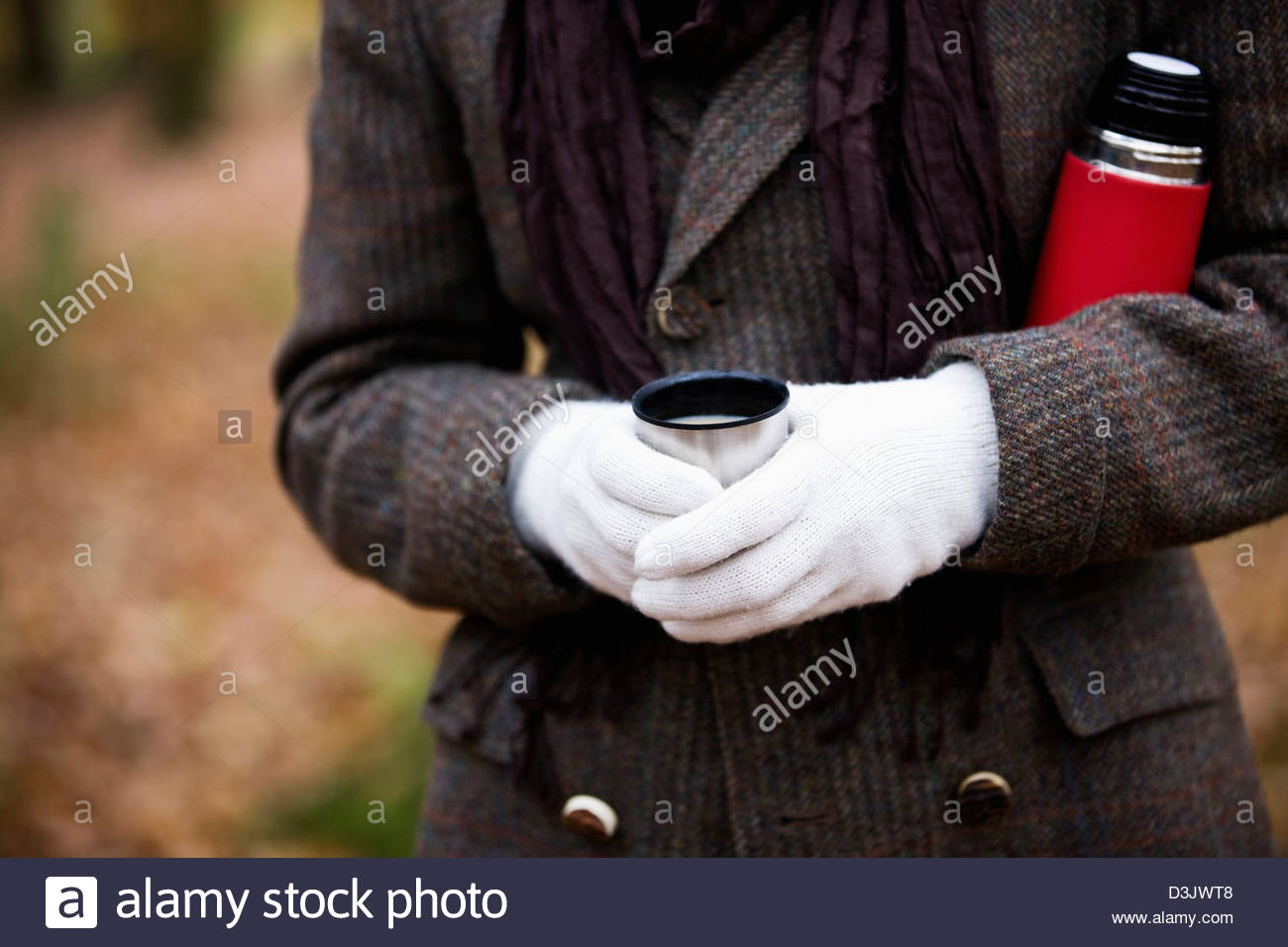 A woman holding a hot drink and flask outside in autumn - Stock Image
