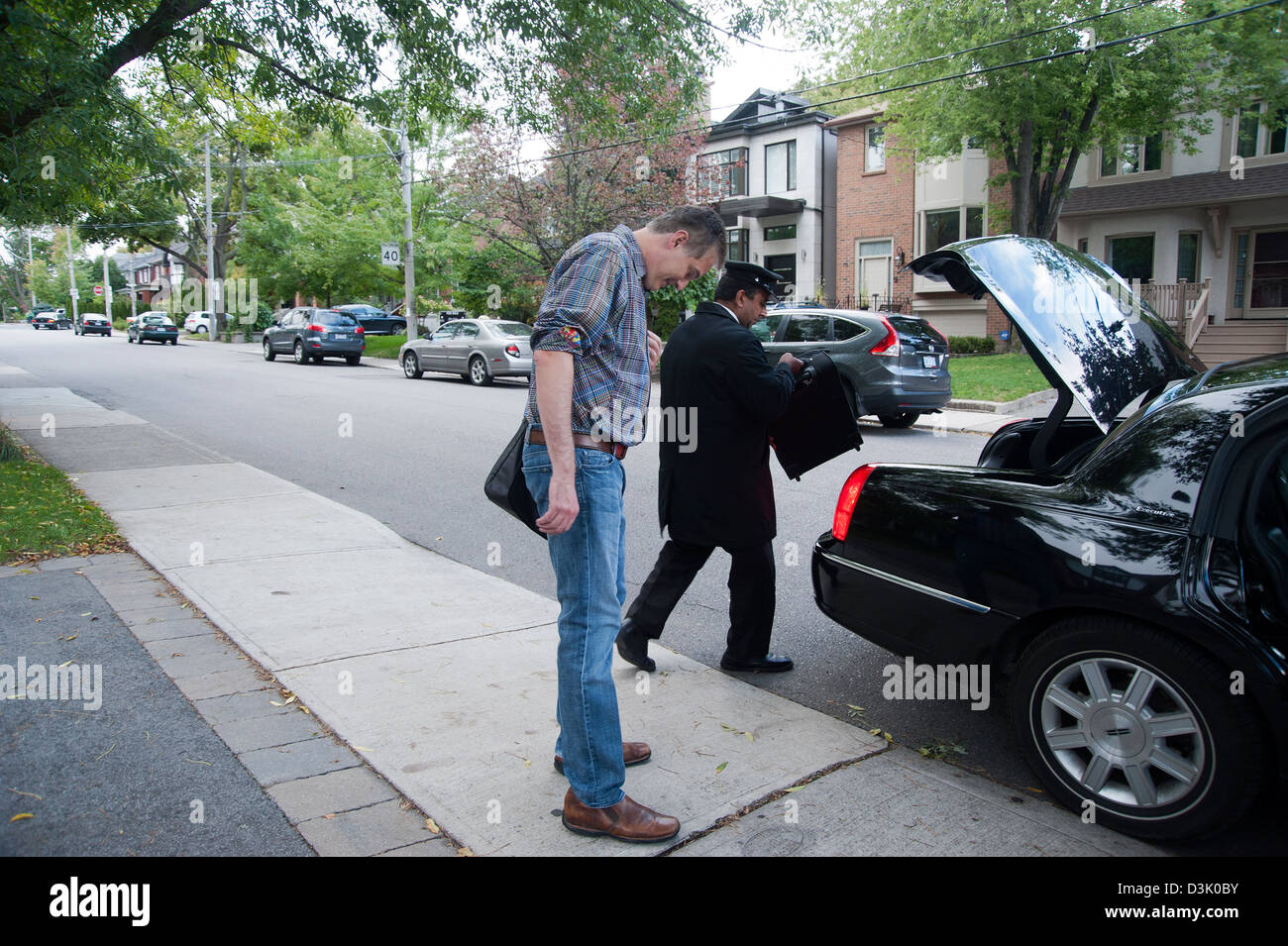 A man waits on sidewalk while uniformed limousine driver puts his luggage in trunk of car - Stock Image