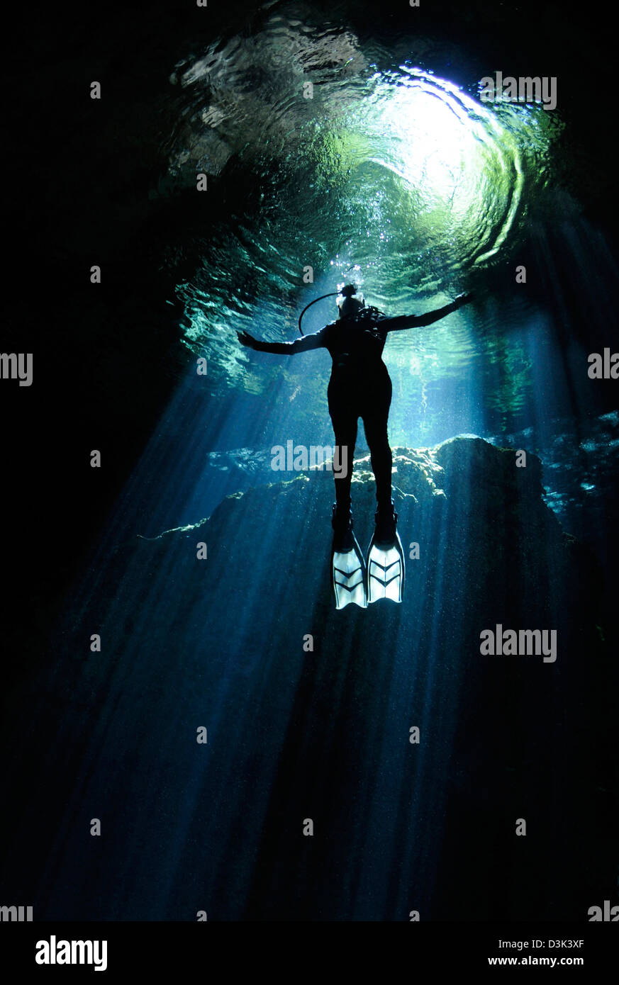 A cavern diver ascends into the light filtering into cenote system at Yucatan Peninsula, Mexico. Stock Photo
