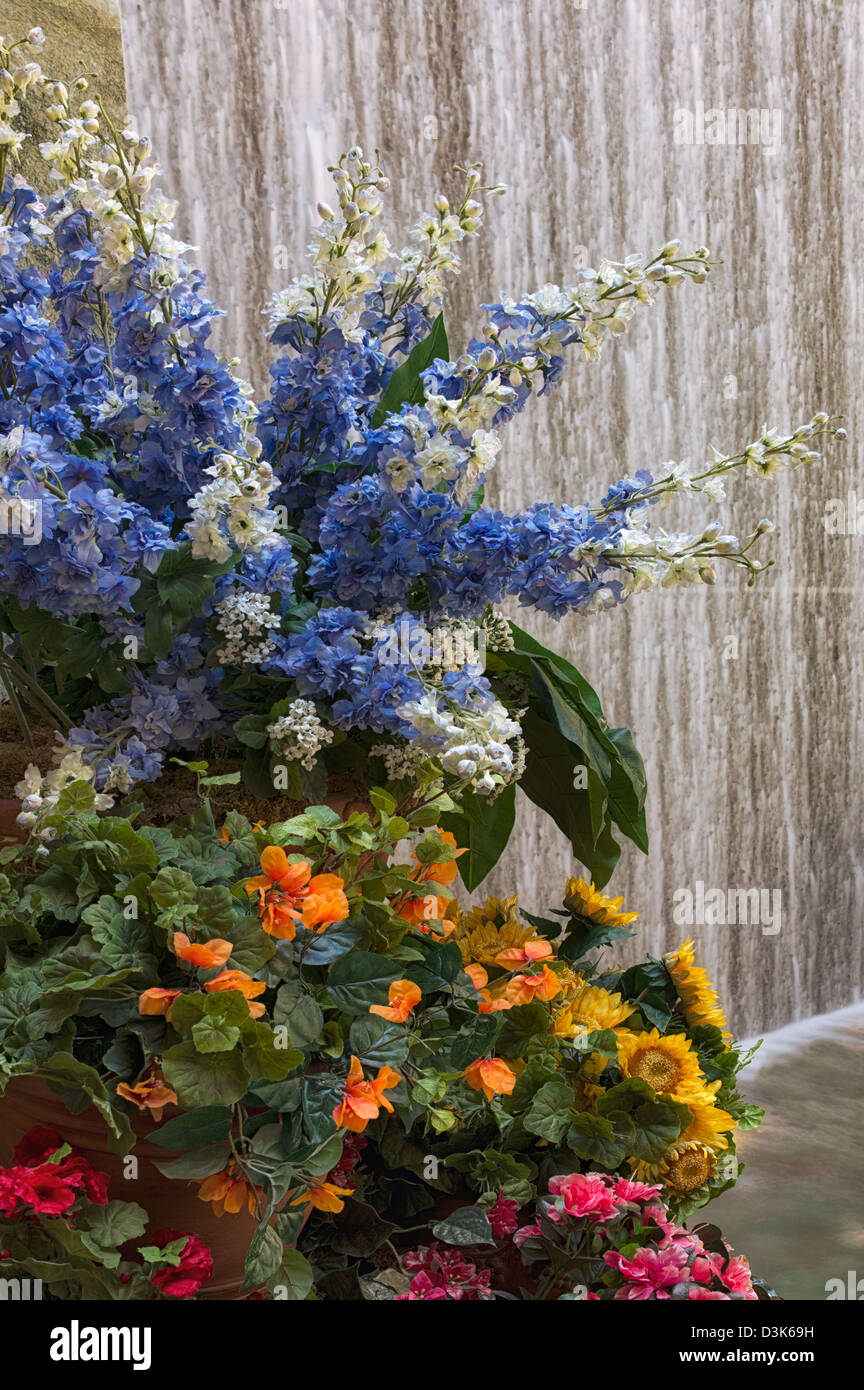 Flowers and waterfall in garden - Stock Image
