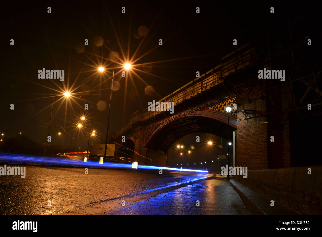 Night scene of car traveling under bridge - Stock Image