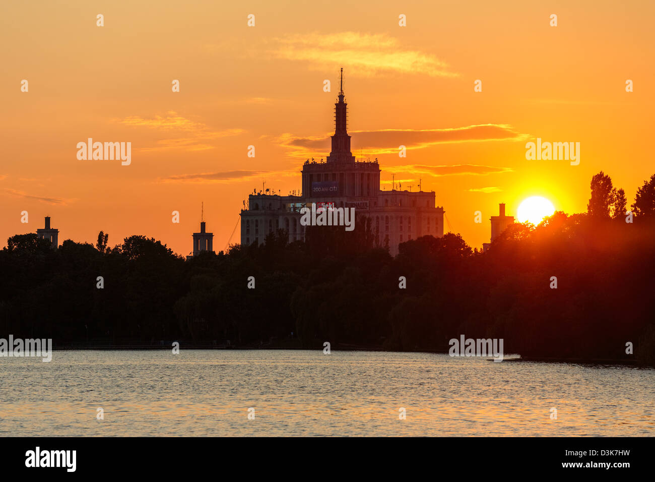 Sunset over House of the Free Press. View from the lake in Herastrau Park, Bucharest, Romania. - Stock Image