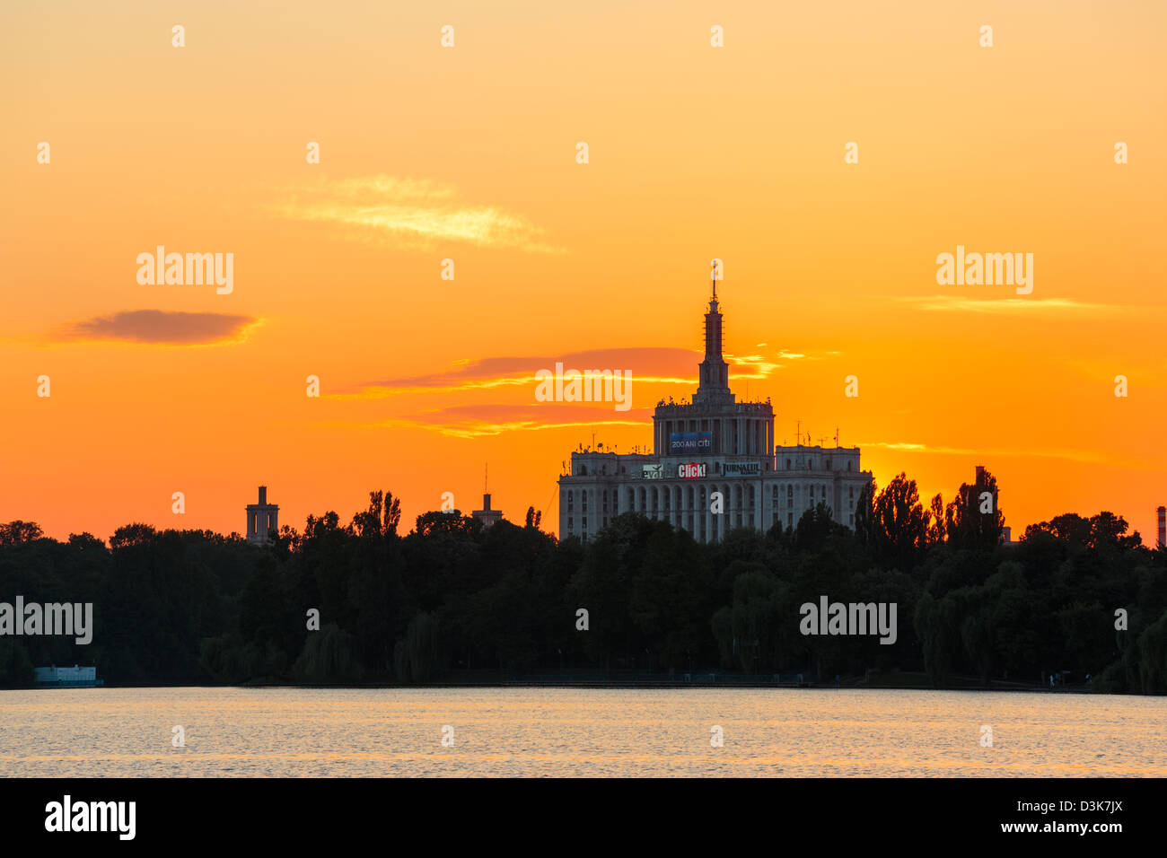 Sunset over House of the Free Press. View from the lake in Herastrau Park, Bucharest, Romania. Stock Photo