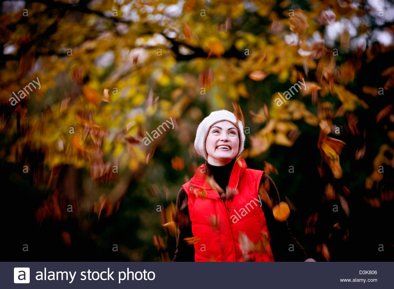 A woman standing amongst falling autumn leaves - Stock Image