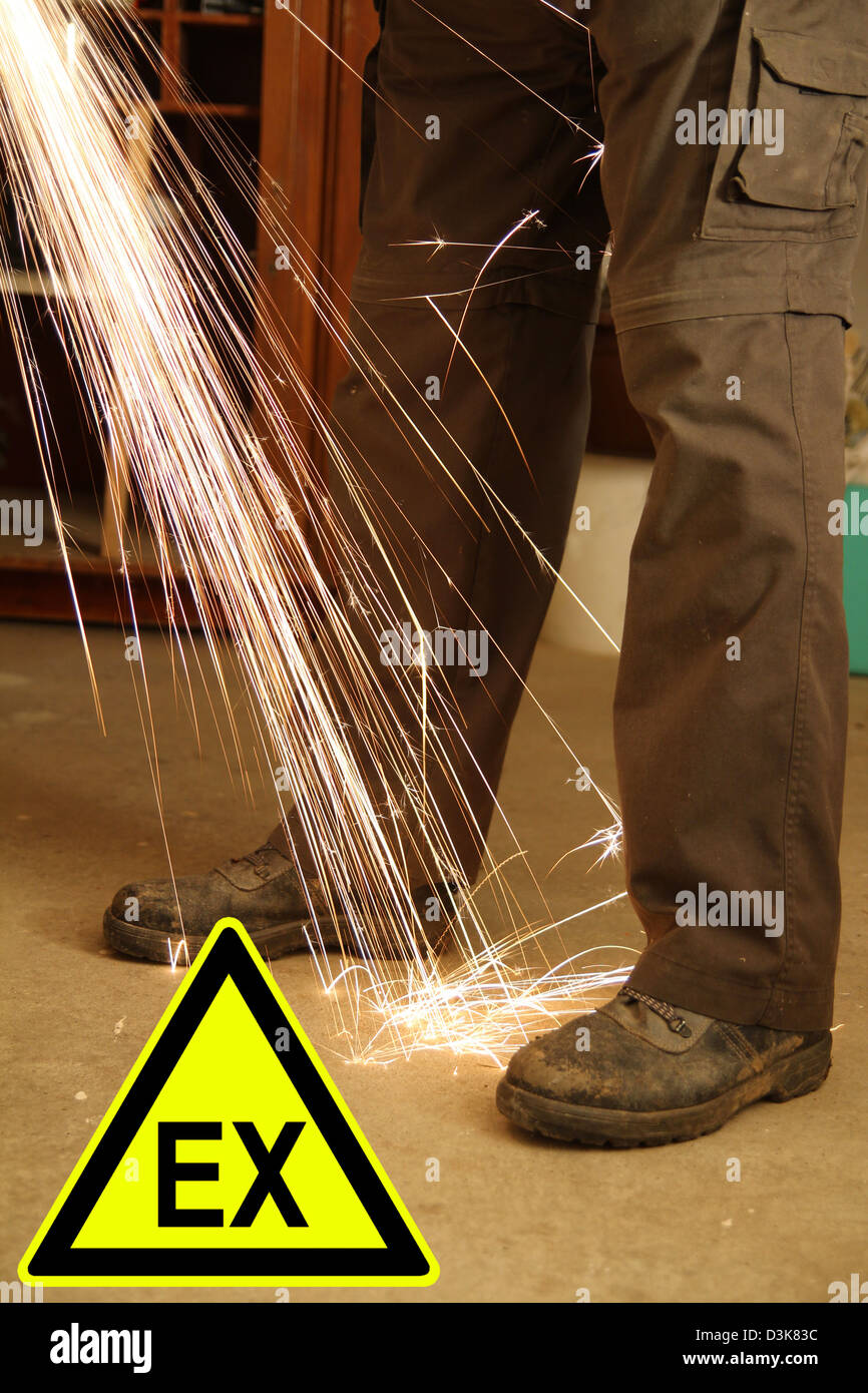 Feets of a worker with sparks of an angle grinder and a sign - Stock Image