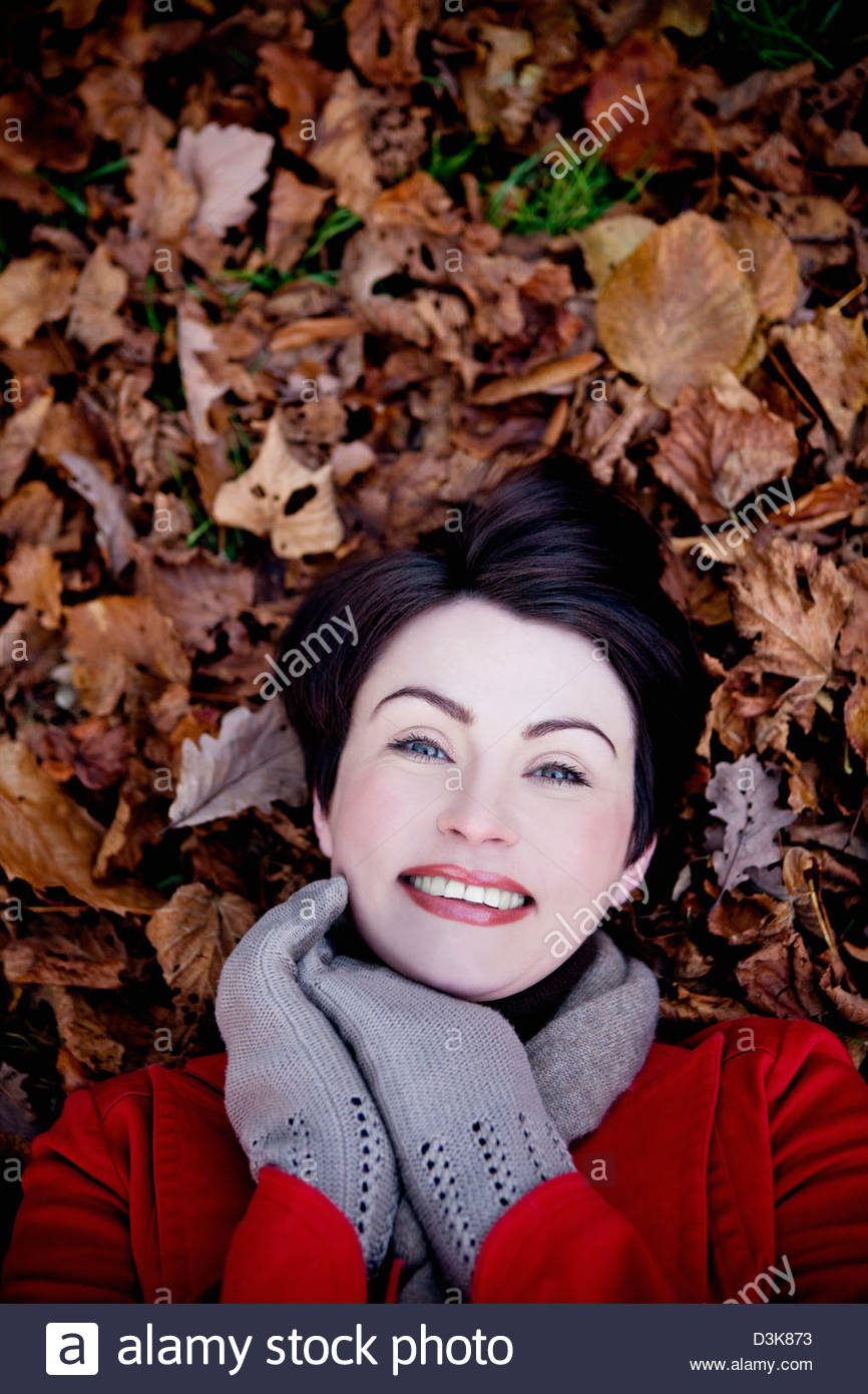 A woman lying amongst autumn leaves - Stock Image