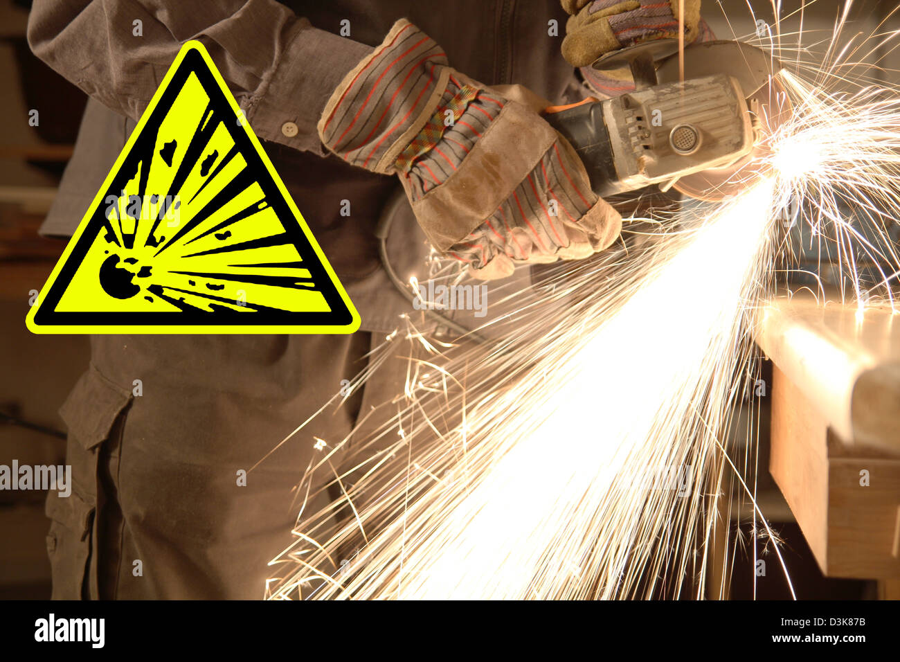 Hands of a worker with angle grinder, sparks and sign - Stock Image
