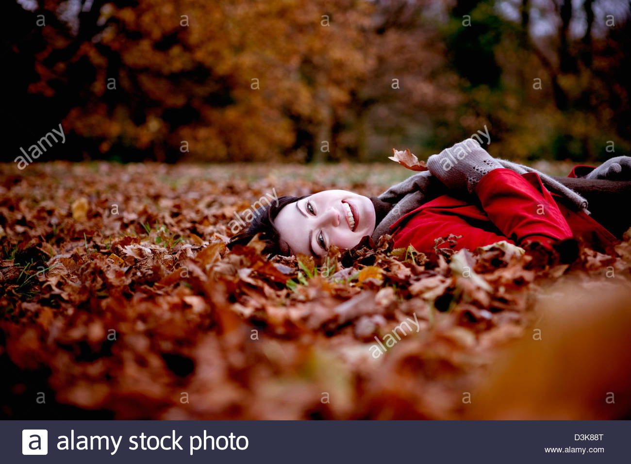 A woman lying on the ground hold an autumn leaf - Stock Image
