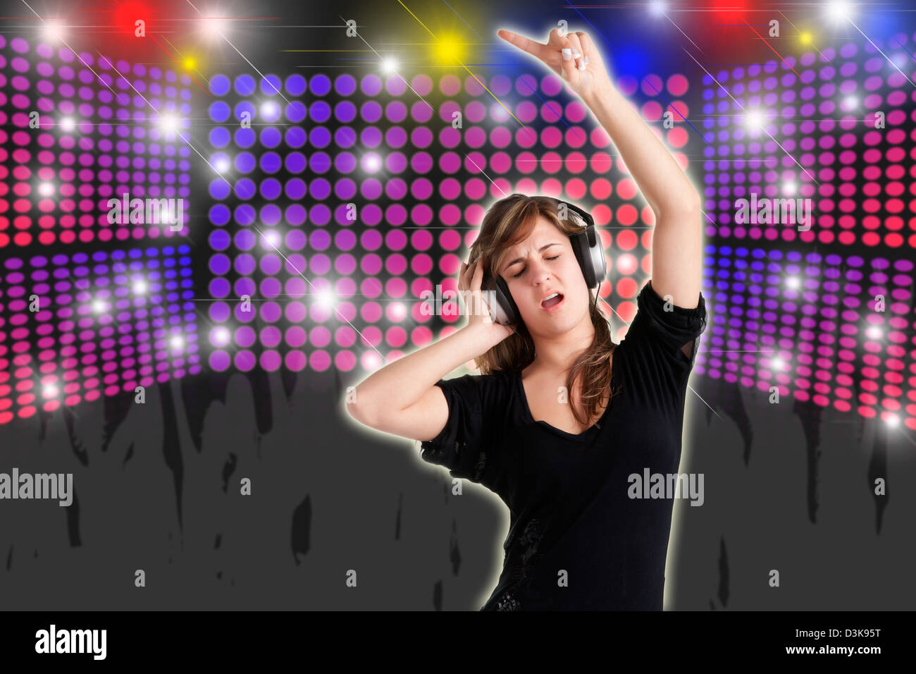 Woman dancing using headphones with disco lights in the background - Stock Image