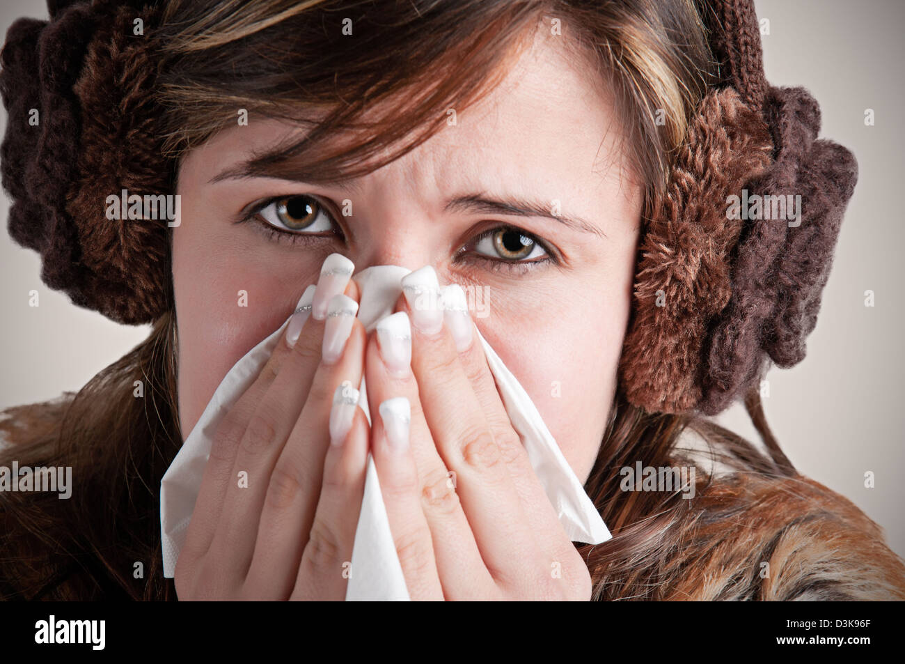 Pale sick woman with a flu, sneezing, in a dark background - Stock Image