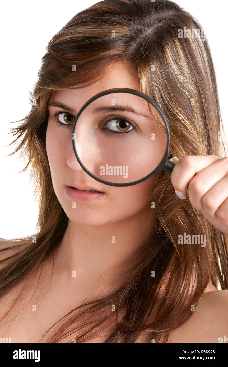 Woman looking trough a magnifying glass, isolated in a white background - Stock Image