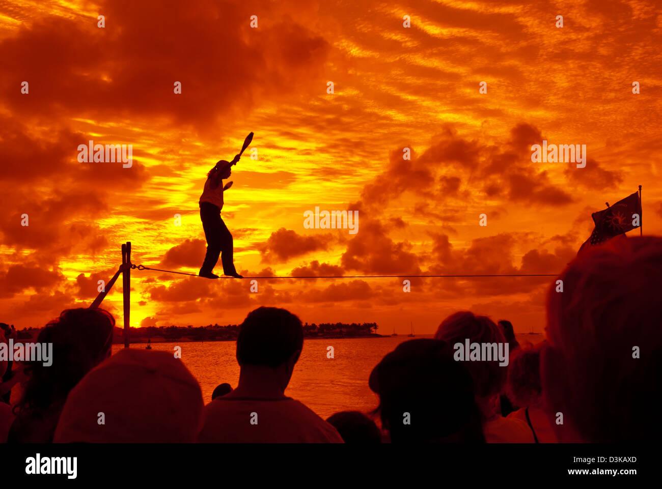 Juggler walks tightrope at Sunset Celebration at Mallory Square, Key West, Florida - Stock Image