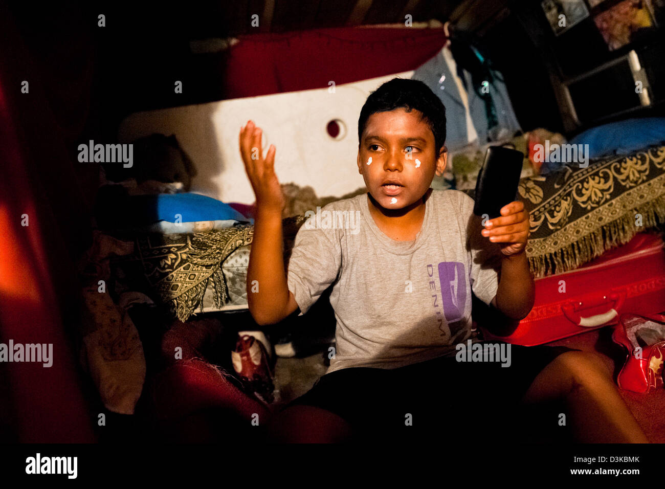 A Salvadorean boy applies makeup before his clown performance at a family run circus travelling in Central America. - Stock Image