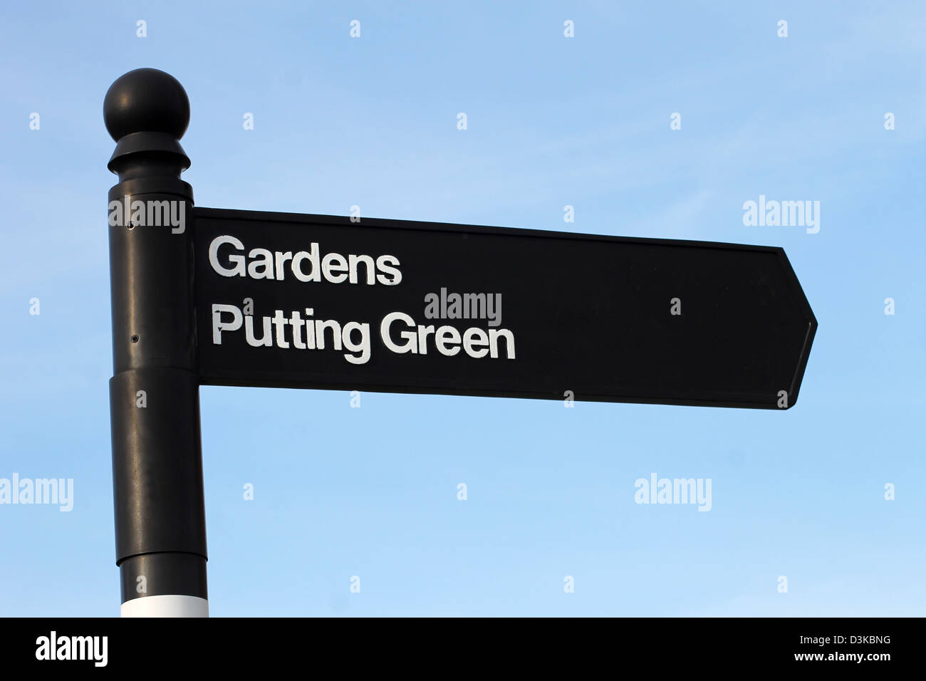 Traditional English gardens and putting green sign, blue sky background. - Stock Image