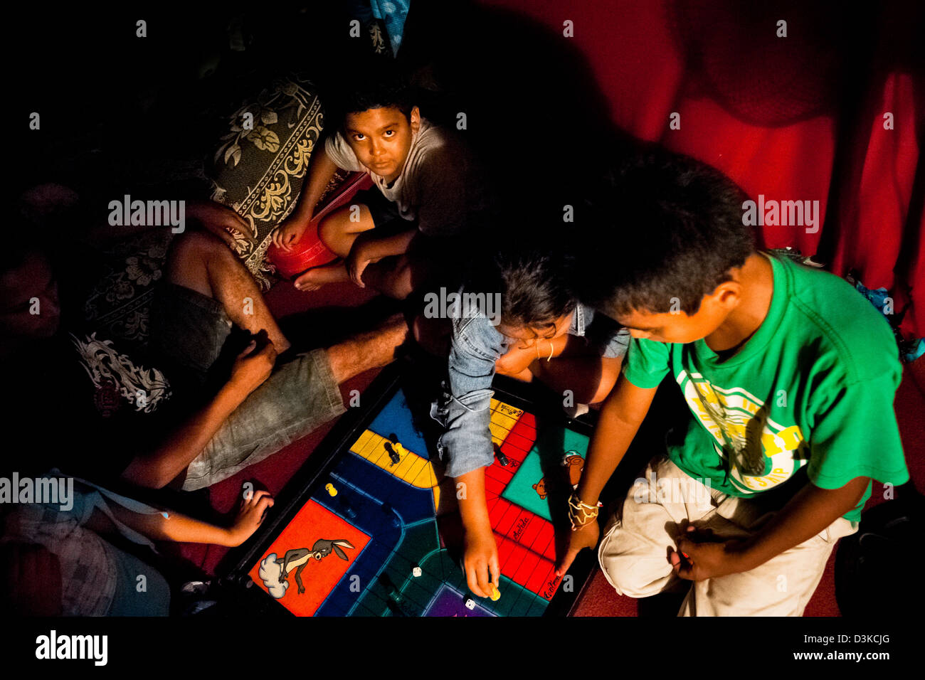 Salvadorean children play a table game in the trailer belonged to a family run circus travelling in Central America. - Stock Image