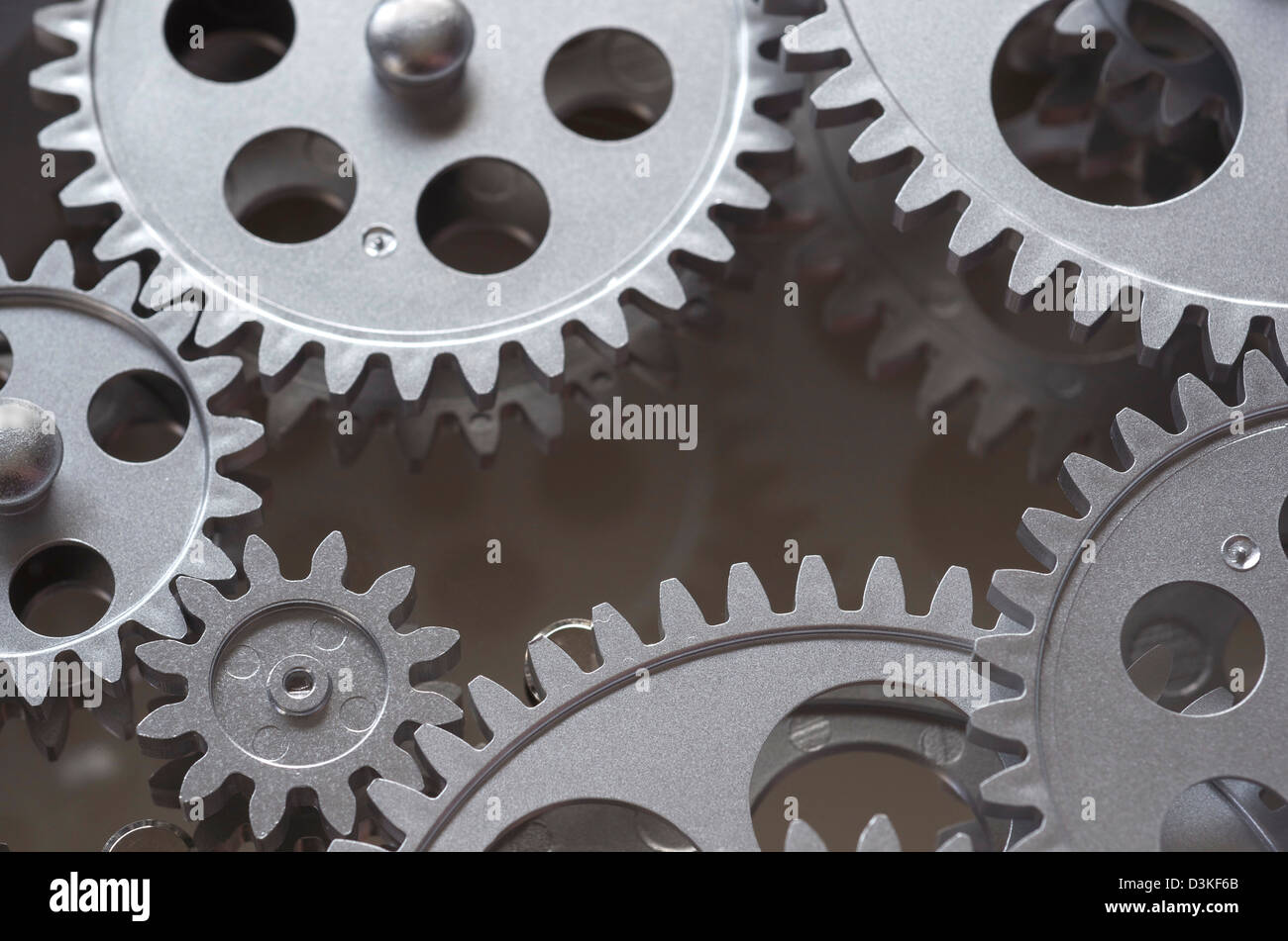 Gears interlocked that are gray, and around the perimeter of the frame with darker reflective area in the center. - Stock Image