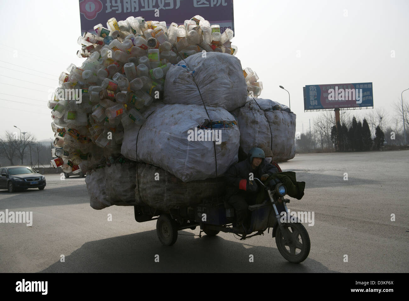 A motor tricycle loaded with recyclable plastic bottles drives along a street in a town in Hebei province, China. - Stock Image