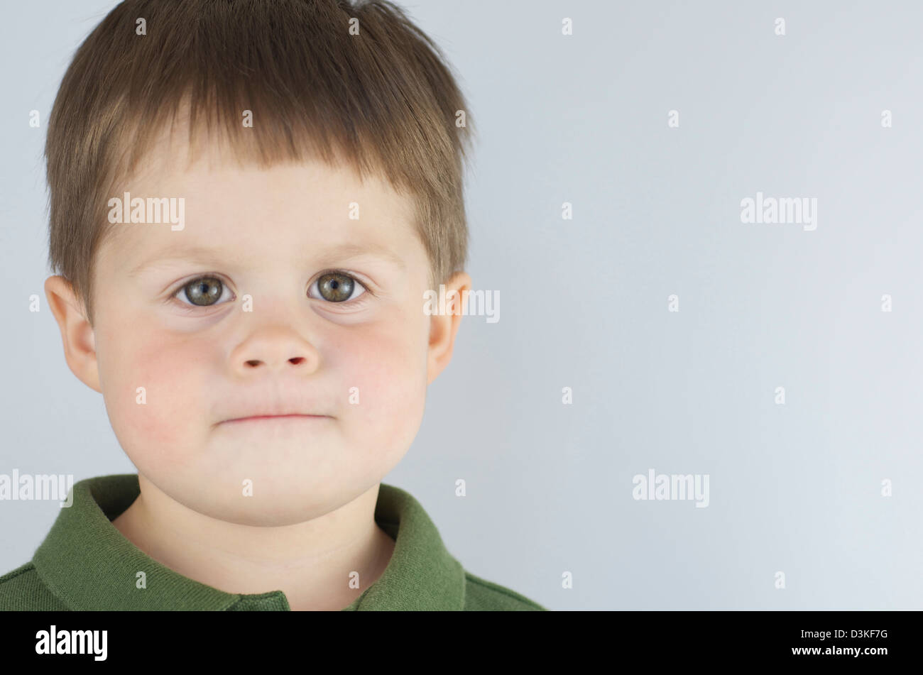 Serious and determined 2 year old boy looking straight at camera, lips pursed with green eyes wide and clear, copy - Stock Image