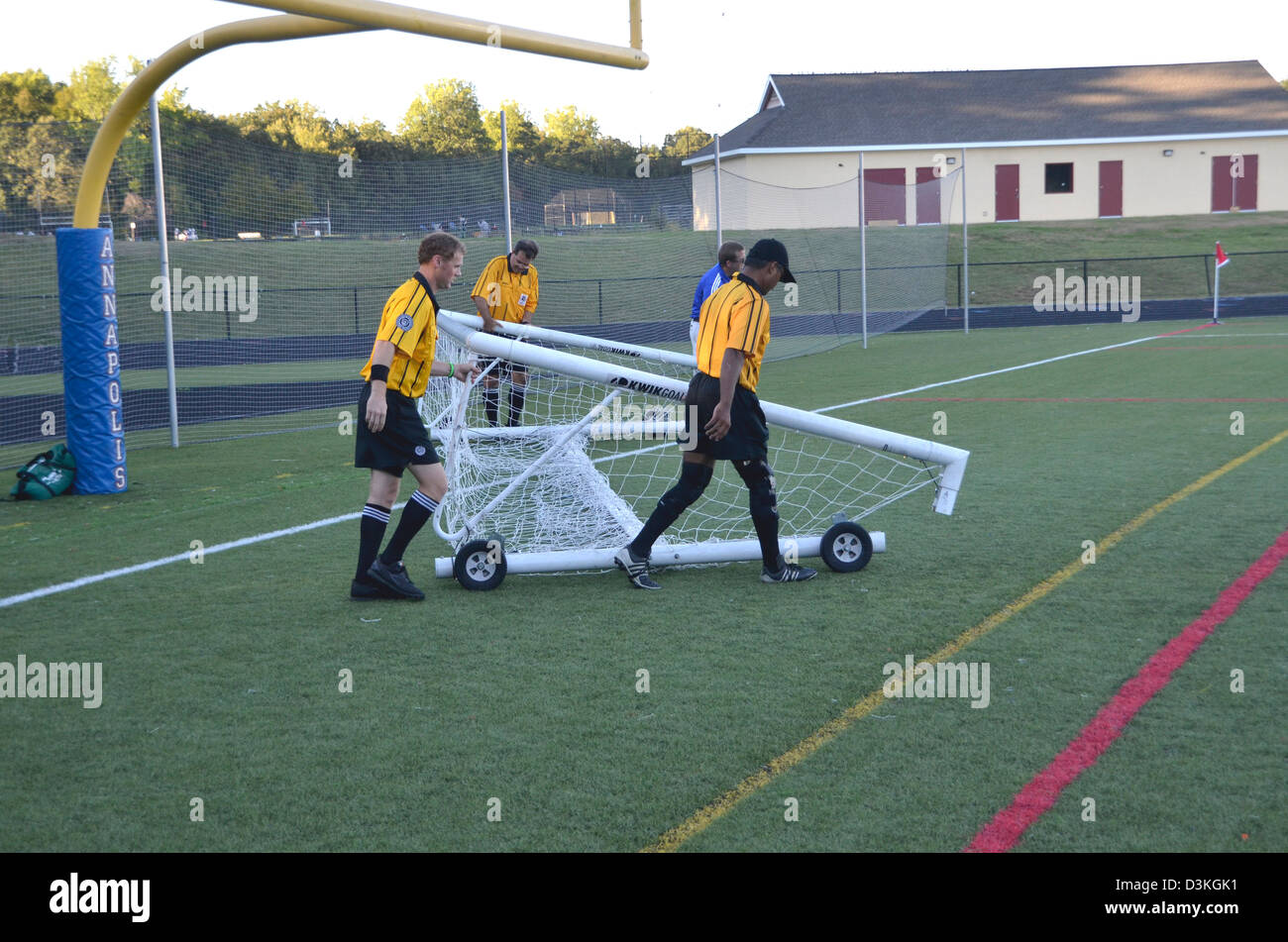 Officials remove a broken net during a lacrosse game - Stock Image
