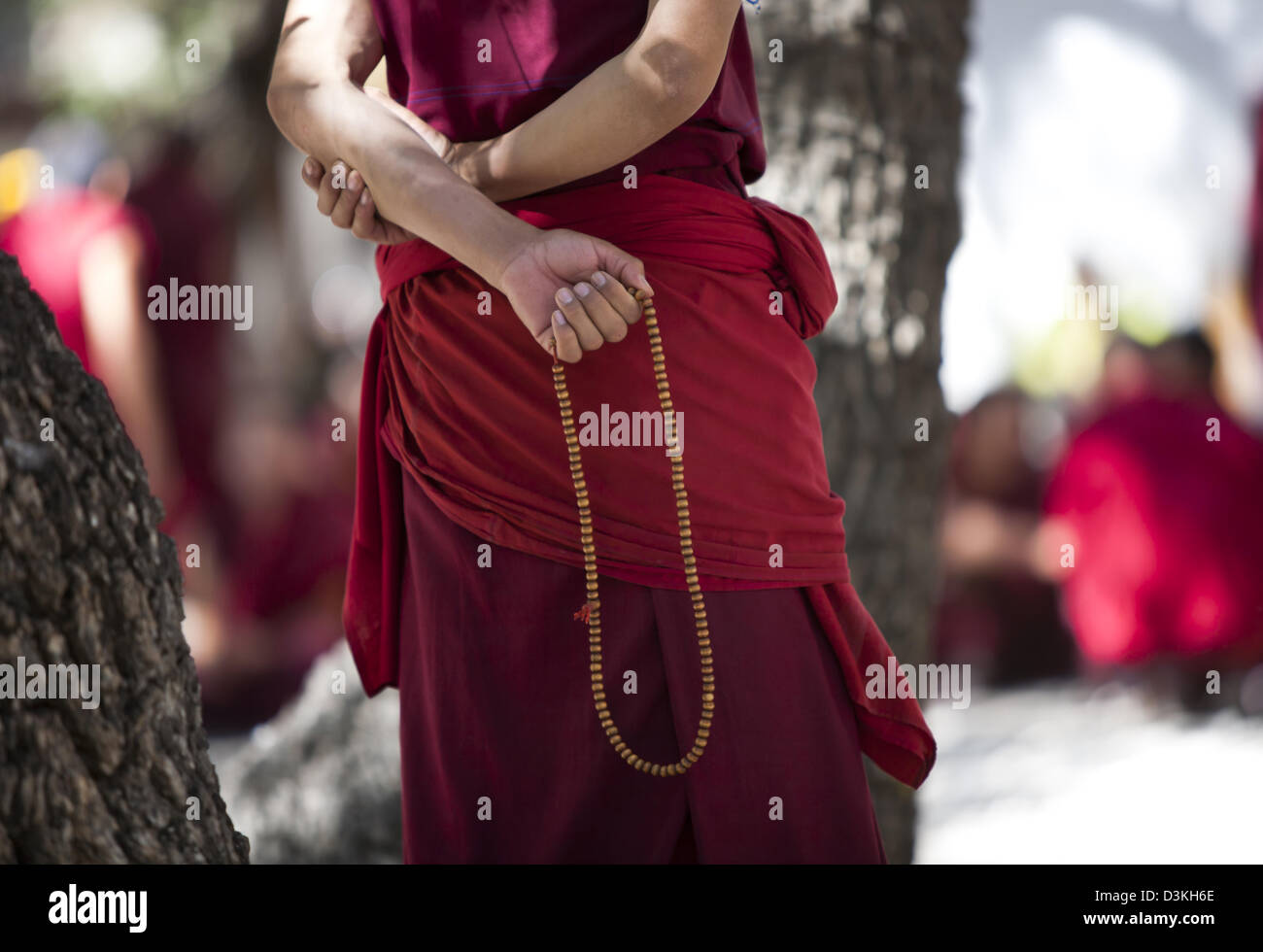 A monk in debate with hands clasped behind back, prayer beads in his hand, Sera Monastery, Lhasa, Tibet. - Stock Image