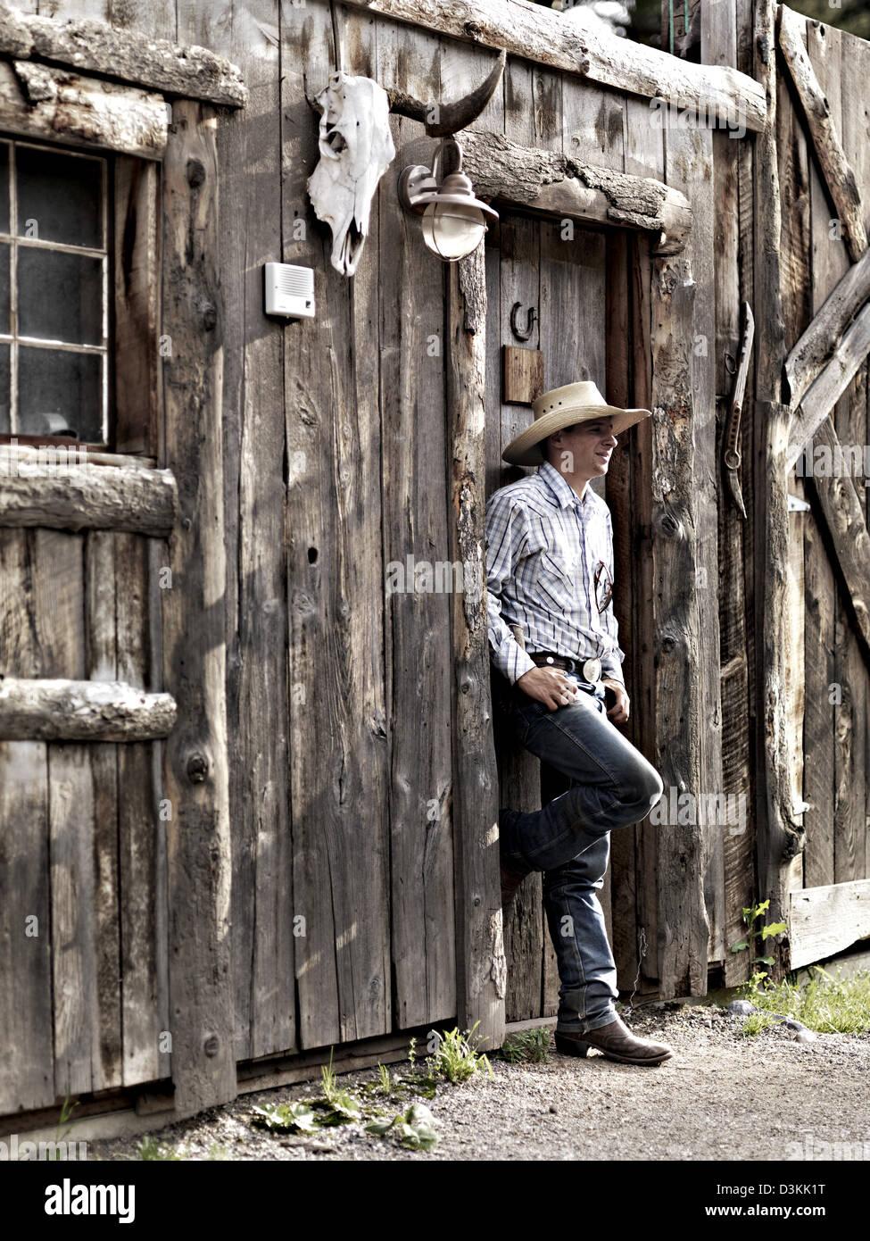 Cowboy stands at exterior of log cabin, Montana, USA - Stock Image