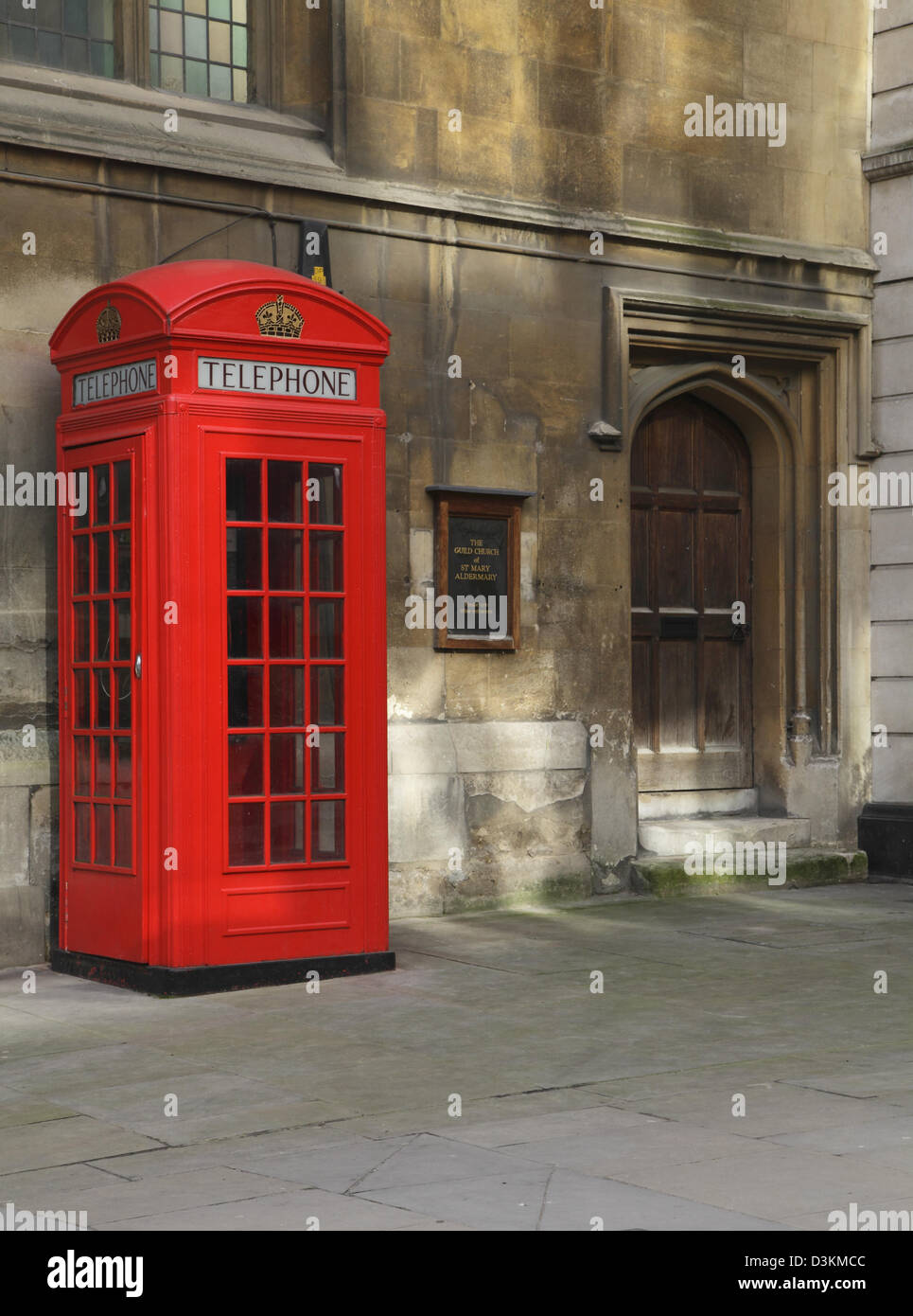 Red telephone box in the City of London by the historic St Mary Aldermary church England UK GB - Stock Image