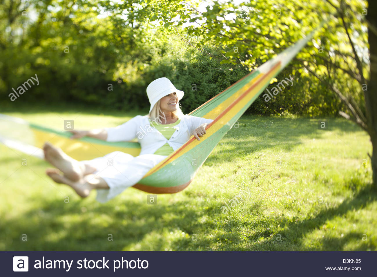 Senior active happy woman relaxing in a hammock - Stock Image