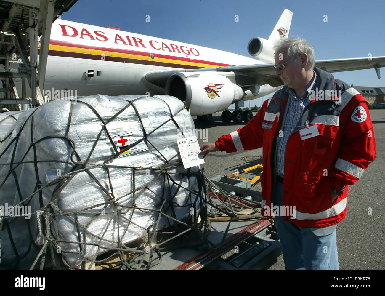 (dpa) - Hans Heinrich Schaefer employee of the German Red cross (DRK) supervises the loading of relief supplies - Stock Image
